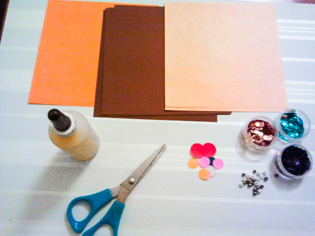 Supplies for making origami cookies. Square paper, glue, embellishments, and scissors (optional).