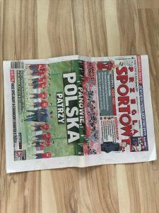 Fold newspaper in half.