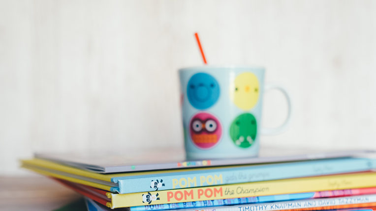 stack of books with child's cup on top