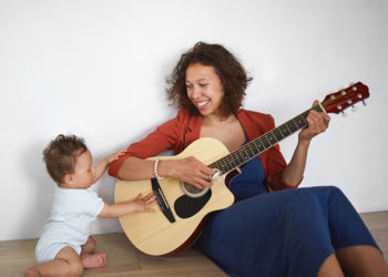 Mother and child playing guitar