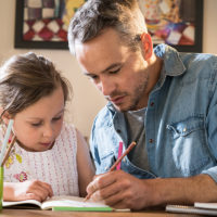 Dad Helping Child with Schoolwork