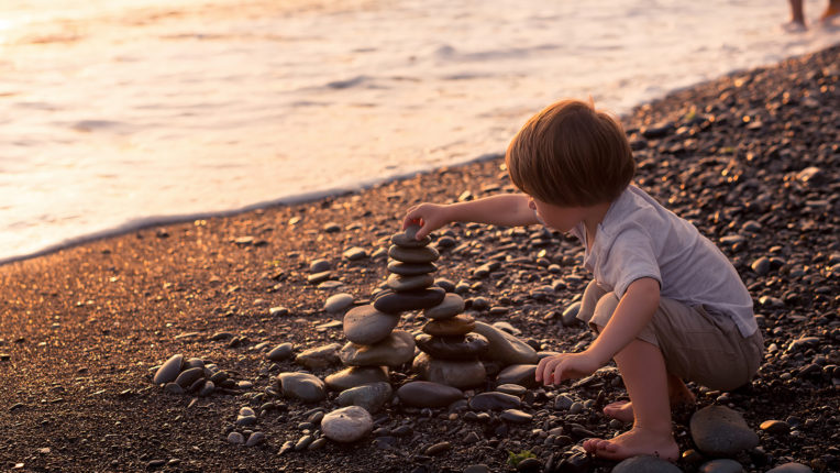 Child Stacking Rocks